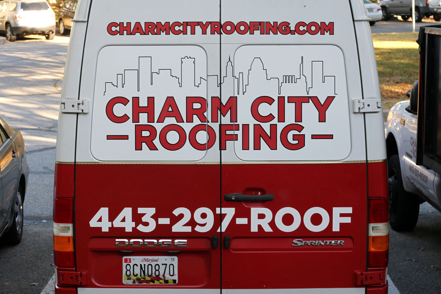 The Charm City Roofing van from the back end while in a court parking space