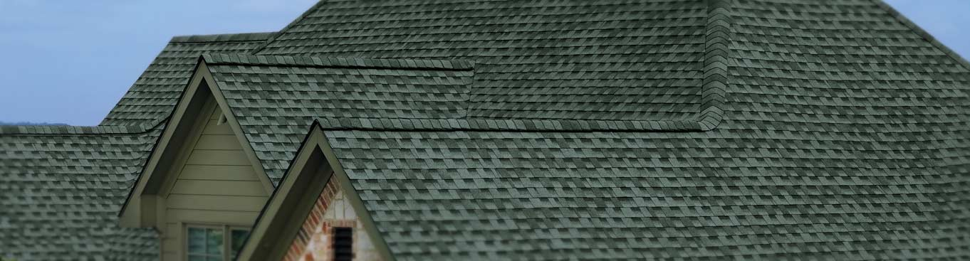 A newly shingled roof with a mix of dark and light green shingles