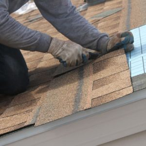 Roofer Cutting Shingles On Rooftop